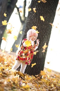 child-playing-with-autumn-leaves